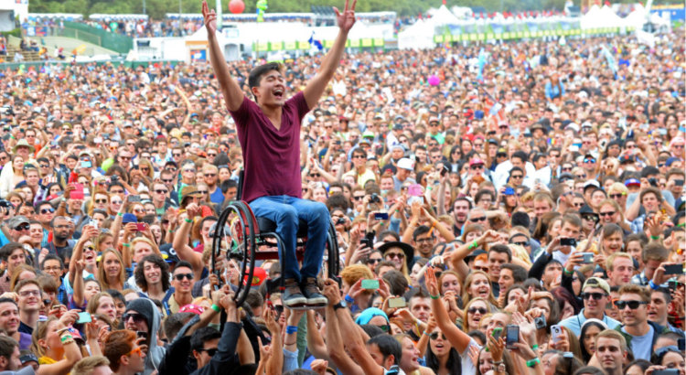 Joyous man with arms raised sitting in wheelchair held aloft by people in very large concert audience